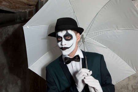 the scars: Evil clown wearing a bowler hat holding white umbrella Stock Photo