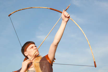 Robin Hood. Young archer in vintage clothes with arrow and long bow Stock Photo