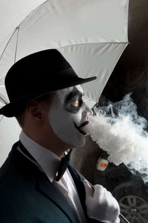 Scary evil clown wearing a bowler hat vaping Stock Photo