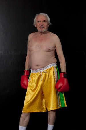 pugilist: Senior boxer man with red gloves on black wall background
