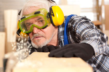 planos electricos: Senior carpenter working in furniture factory