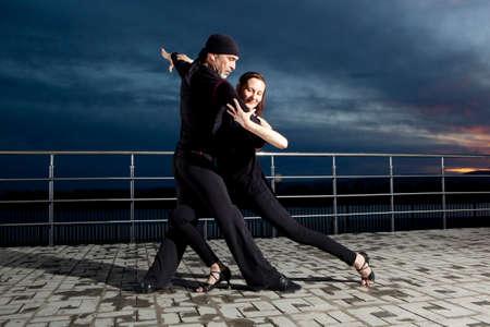 Senior couple ballroom dancing on dark sunset background
