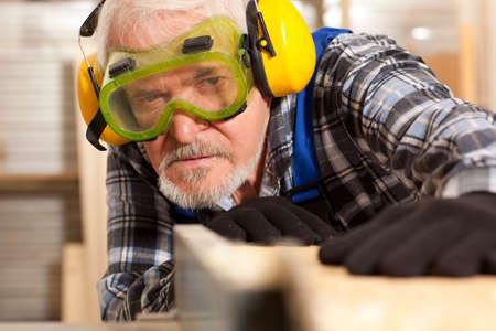 Senior carpenter working in furniture factory