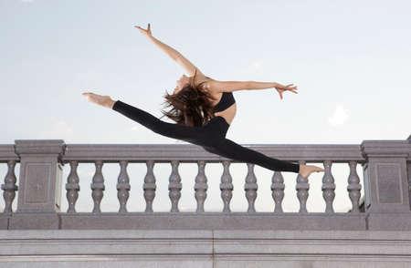 Ballet dancer in black body series on sky background
