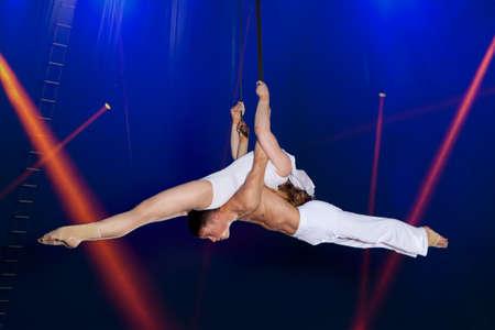 Couple circus air gymnast on dark blue background