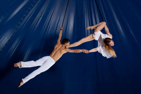 Couple circus air gymnast on dark blue background