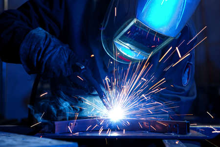 Welder erecting technical steel. Industrial steel welder in factory technical