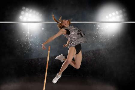 Competition pole vault jumper female on stadium at night background Stockfoto