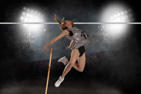 Competition pole vault jumper female on stadium at night background Foto de archivo