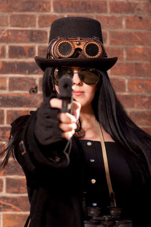 subculture: Portrait of a beautiful steampunk woman holding a gun