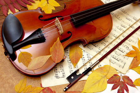 Violin in vintage style on wood, notes, autumn leaves background Stock Photo