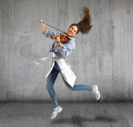 Woman playing violin on grey background 스톡 콘텐츠