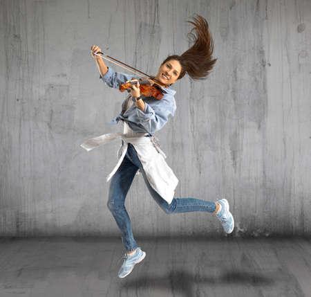 Woman playing violin on grey background Stok Fotoğraf