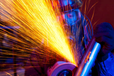 Worker using a grinder. Industrial steel in factory technical Stock Photo