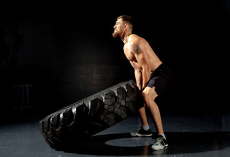 Crossfit training. Muscular young man flipping tire at gym Foto de archivo - 95318710