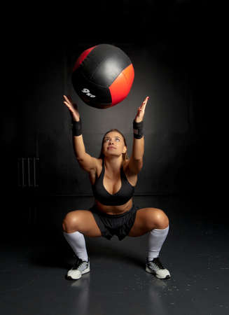 Muscular fit woman working out with medicine ball