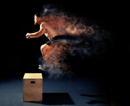 Man jumping on fit box in gym. Male with torso exercises jump on the dark background. Stockfoto