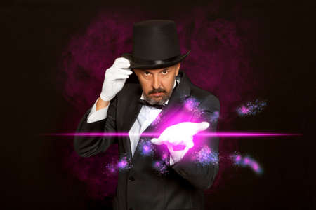 Magician in top hat showing trick on black background