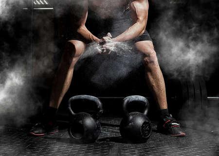Mani d'applauso del sollevatore di pesi e prepararsi per l'allenamento in una palestra. Concentrati sulla polvere