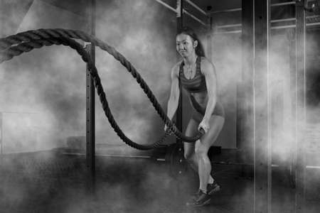 Woman working out with battle ropes at gym Imagens