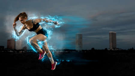 Woman sprinter leaving starting blocks on the athletic track. Exploding start
