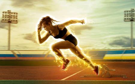Woman sprinter leaving starting blocks on the athletic track. Exploding start