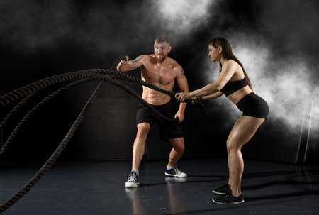 Woman and men working out with battle ropes at gym 免版税图像