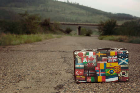 Vintage brown threadbare suitcase with collection of retro travel flag labels