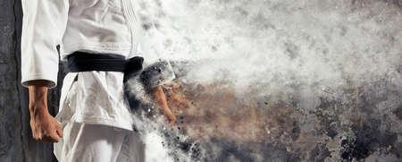 Facet pozuje w białym kimono z czarnym paskiem. Japoński sztandar judo