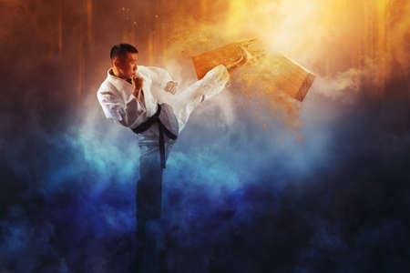 Determined Karate man breaking with leg wooden board