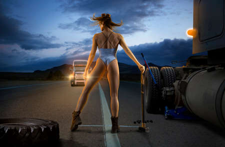 Beautiful woman trucker replace tire on wheel on road