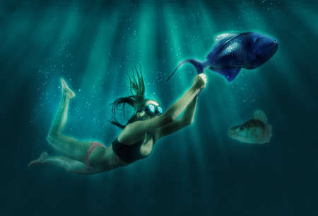 Fashionable and athletic girl diver alone in the depths of the ocean