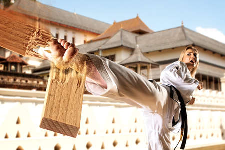 Caucasian female in kimono practicing taekwondo. Breaking board. Modern Korean martial art similar to karate