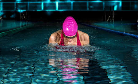 Woman in swimming pool. Breaststroke swimming style