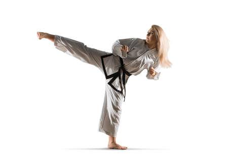Woman in kimono practicing taekwondo. Isolated on white background