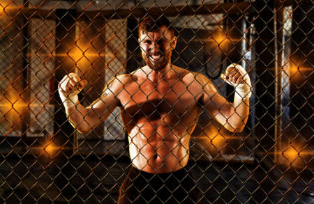 Strong mixed martial arts fighter inside the cage. Portrait of a MMA fighter