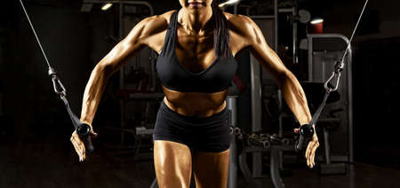 Fitness woman execute exercise with exercise-machine cable crossover in gym. Golden skin retouch