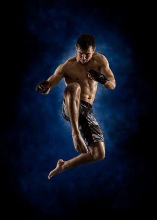 MMA male fighter jumping with a knee kick