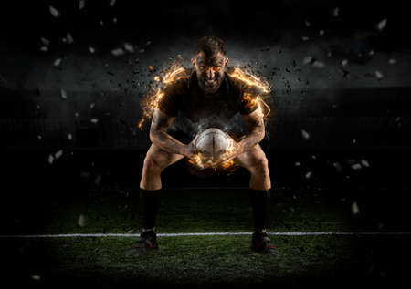 Rugby player in action on dark arena Imagens