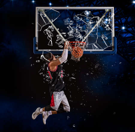 Shattered backboard. Basketball player players in action. Basketball concept on dark background