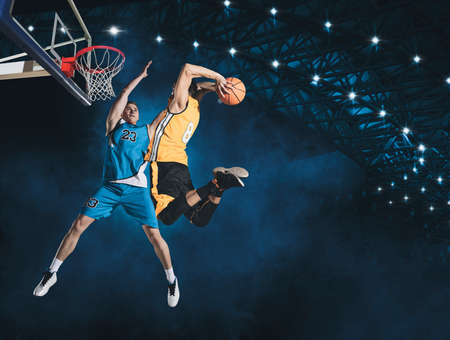 Two basketball players in action in arena. Blocked shot