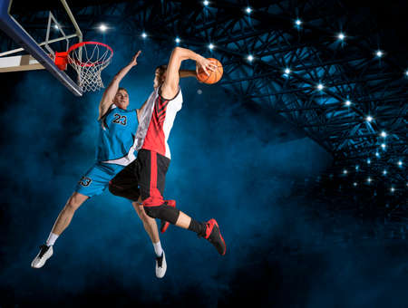 Two basketball players in action in arena. Blocked shot Reklamní fotografie
