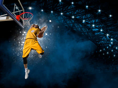 Basketball player players in action. Basketball concept on dark smoke background