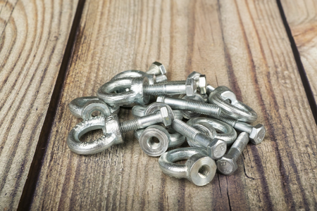 ring nuts with bolts, zinc plated on wooden background.