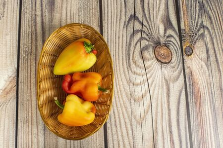 Sweet pepper in a wicker basket on a wooden table. Autumn harvest thanksgiving Day. Stock Photo