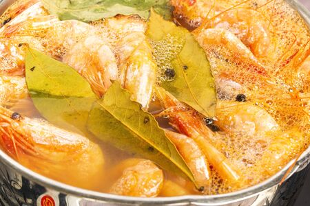 Atlantic prawns are cooked with Bay leaf and allspice in a stainless steel pan. Zdjęcie Seryjne