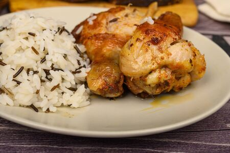Chicken legs with spices fried in a cauldron, Served on a plate with rice.