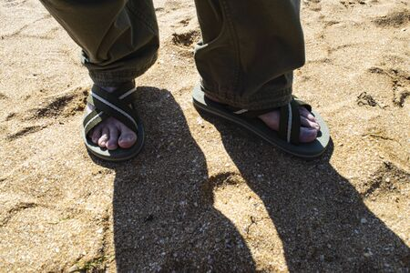 Men's legs in long trousers and Slippers on the sandy beach