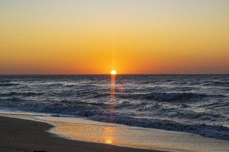 Sunrise over the Black sea, waves on the sandy beach Stock fotó