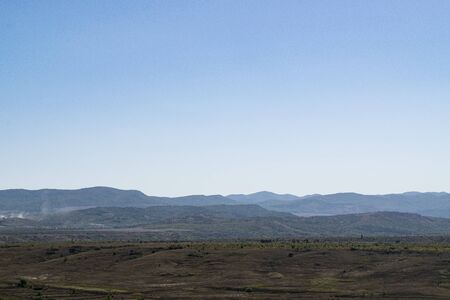 Crimean landscape. Steppe in the foreground and mountains covered with fog in the background Reklamní fotografie